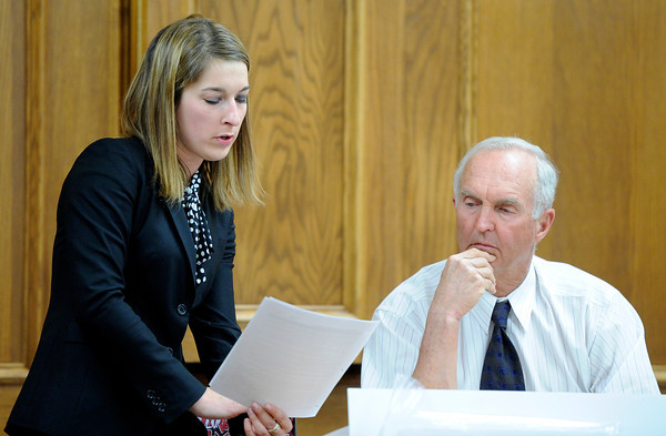 Defense attorney Kathryn Herold shows a piece of evidence to Rita Redford's friend John Moore while cross-examining him on Friday, March 16, during the third day of the Adam Raszynski murder trial at the Boulder County Justice Center in Boulder. Raszynski is on trial for the murder of his mother Rita Redford.<br /> Jeremy Papasso/ Camera