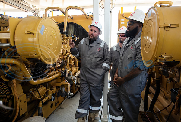 Motor men Chad O'Brien, Charlie Graham and Marcus Edwards talk about the generators in the Norseman II Series Scan Titan drilling rig during a public tour on Monday, March 18, 2019 at the Scandrill rig-up yard in Tyler.   (Sarah A. Miller/Tyler Morning Telegraph)