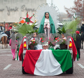Diana Alfaro, 13, of Tyler, wears a green shaw as she portrays the Virgin Mary while riding a float during a parade in downtown Tyler, Texas Sunday in celebration of the The Day of the Virgin of Guadalupe Catholic feast, which is observed Dec. 12. The parade was organized by the St. Peter Claver Catholic Church in Tyler. The feast day celebrates a vision Juan Diego had the morning of December 9, 1531 in Mexico City of a young girl he recognized as the Virgin Mary.