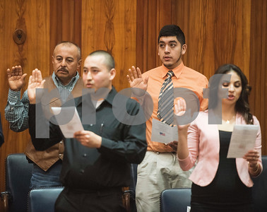 Antonio Rojas of Tyler, center, formerly of Mexico, gives his oath during a naturalization ceremony held at the United States District Court for the Eastern District of Texas in Tyler Thursday morning. Forty immigrants from 17 different countries became United States citizens during the ceremony.  (Sarah A. Miller/Tyler Morning Telegraph)