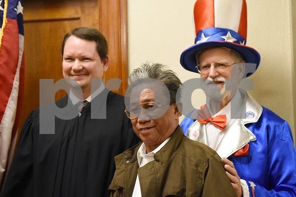 New Gladewater citizen Leonardo Narvasa, formerly of the Philippines, takes a photo with U.S. Magistrate Judge John D. Love and Gerry Kuklewicz dressed as Uncle Sam after a naturalization ceremony held at the United States District Court for the Eastern District of Texas in Tyler Thursday morning. Forty immigrants from 17 different countries became United States citizens during the ceremony.  (Sarah A. Miller/Tyler Morning Telegraph)
