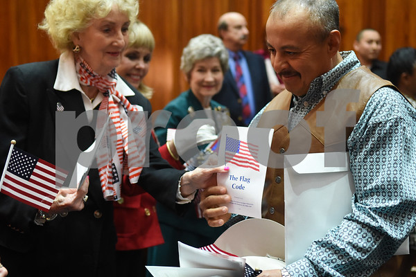 Eduardo Sosa of Tyler receives pamphlets and an American flag during a naturalization ceremony held at the United States District Court for the Eastern District of Texas in Tyler Thursday morning. Sosa immigrated to the United States from Mexico.  (Sarah A. Miller/Tyler Morning Telegraph)