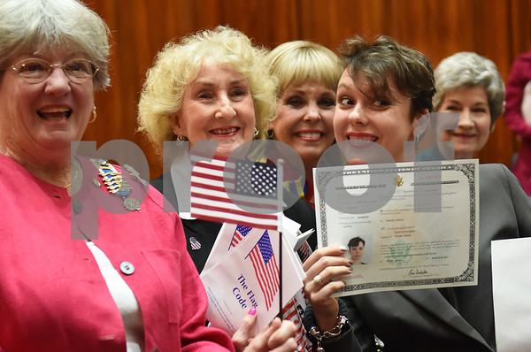 Dace Lucia Kidd of Tyler, far right, formerly of Latvia, holds her certificate after a naturalization ceremony held at the United States District Court for the Eastern District of Texas in Tyler Thursday morning. Forty immigrants from 17 different countries became United States citizens during the ceremony.  (Sarah A. Miller/Tyler Morning Telegraph)