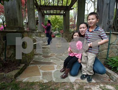 Christina Stevens of Gladewater and her children Claire, 3, and Caleb, 5, look at the azaleas in Guy and Joan Pyron's yard on Dobbs Street. The Pyrons will host the opening ceremony of the Azalea & Spring Flower Trail Friday at 10 a.m.  (Sarah A. Miller/Tyler Morning Telegraph)