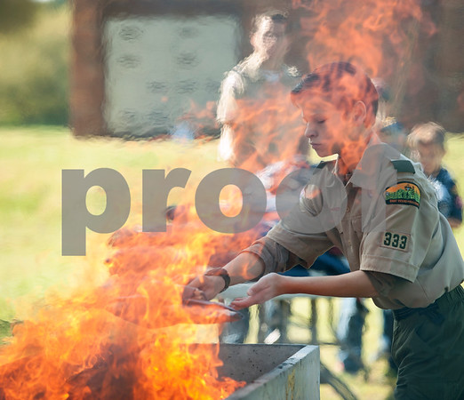 Boy Scout Bradley Richbourg, 12, places a United States flag into the fire during a retirement ceremony held by The Capt. William Barron Chapter of the Sons of the American Revolution Saturday March 26, 2016 at the Tyler Memorial Cemetery. Cub Scouts from Pack 333 assisted in the ceremony. Over three-hundred torn and faded United States flags were retired.  (Sarah A. Miller/Tyler Morning Telegraph)