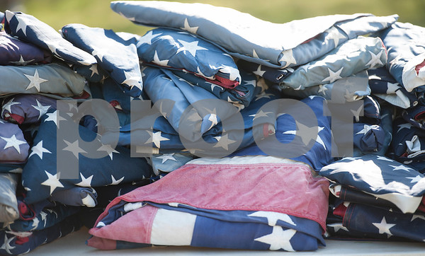 Worn and tattered United States flags are placed on a table before being retired during a ceremony held by The Capt. William Barron Chapter of the Sons of the American Revolution Saturday March 26, 2016 at the Tyler Memorial Cemetery. Cub Scouts from Pack 333 assisted in the ceremony. Over three-hundred torn and faded United States flags were retired.  (Sarah A. Miller/Tyler Morning Telegraph)