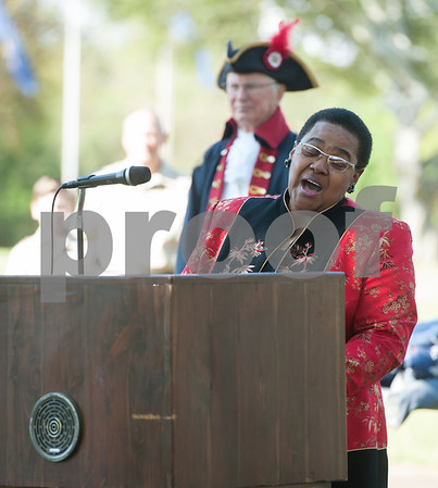 """Debra Hammons sings """"God Bless America"""" during a flag retirement ceremony held by The Capt. William Barron Chapter of the Sons of the American Revolution Saturday March 26, 2016 at the Tyler Memorial Cemetery. Cub Scouts from Pack 333 assisted in the ceremony. Over three-hundred torn and faded United States flags were retired.  (Sarah A. Miller/Tyler Morning Telegraph)"""