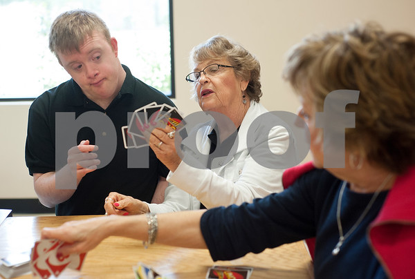 photo by Sarah A. Miller/Tyler Morning Telegraph  Volunteer Kathy Stetson of Tyler, center, helps Matthew Carter look through his deck of cards as they play a game of Uno at Achieving Dreams Wednesday. Achieving Dreams is a new day program for adults with special needs that meets in Tyler.