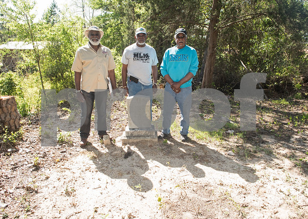 Brothers Eddie Turner, Wilson Turner and Gene Turner along with Hugh Mitchell (not pictured) uncovered the cemetery at the former Dickson Colored Orphanage grounds in Gilmer, Texas. Pictured Thursday March 31, the Gilmer brothers stand next to a headstone they found.  (Sarah A. Miller/Tyler Morning Telegraph)