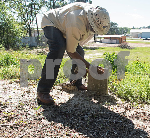Eddie Turner wipes dirt off a headstone at the Dickson Colored Orphanage cemetery in Gilmer, Texas.   (Sarah A. Miller/Tyler Morning Telegraph)