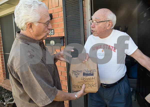 "Meals on Wheels Ministry volunteer Michael Rogers gives Charles Holmen an additional two shelf stable meals with his warm meal Thursday March 30, 2017. Meals on Wheels Ministry currently serves 3,000 seniors and homebound individuals in 30 communities across six counties including Gregg, Henderson, Smith, Upshur, Van Zandt, and Wood counties. ""This really made my day,"" Holmen said.  (Sarah A. Miller/Tyler Morning Telegraph)"