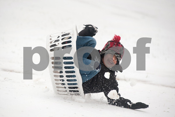 photo by Sarah A. Miller/Tyler Morning Telegraph  Ian Hernandez, 7, of Tyler, tips over as he sleds down a hill at Woldert Park in Tyler in a laundry basket Monday afternoon.