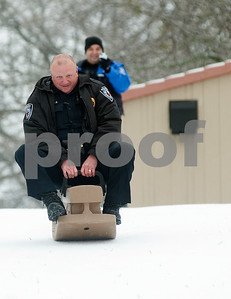 photo by Sarah A. Miller/Tyler Morning Telegraph  Tyler Police Officer Rich Strother rides a makeshift sled belonging Tyler resident Juan Hernandez and his family (not pictured) at Woldert Park in Tyler Monday. Police officers Strother and Luis Aparlclo made a stop at the park and took a few minutes to spend time with Hernandez's  family and kids who were enjoying a day off from work and school due to the winter weather unusual to Tyler, Texas.
