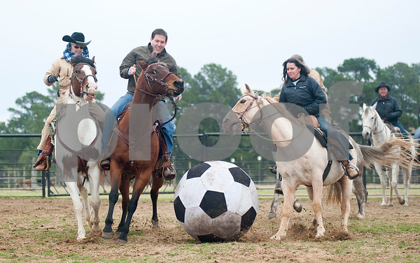photo by Sarah A. Miller/Tyler Morning Telegraph  Brenda Jones of Maydelle, Justin Reeves of Longview and Kathy Hawkins of Diana play in a male versus female game of Cowboy Mounted Soccer at the 1836 Chuckwagon Race Festival held at Diamond B Ranch in Neches, Texas Wednesday. The event celebrates Texas Independence Day Weekend sanctioned chuckwagon races March 7-9 and camping and other events throughout the week such as concerts, trail rides, a mounted shooting clinic and a dutch oven cooking class.