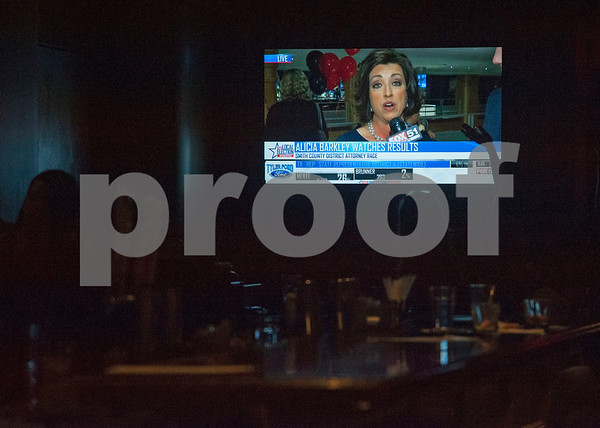 People at the bar at Jack Ryan's watch Smith County District Attorney candidate Alicia Barkley as she is interviewed live on TV from across the room during her election night watch party held at Jack Ryan's in downtown Tyler on Tuesday March 6, 2018.  (Sarah A. Miller/Tyler Morning Telegraph)