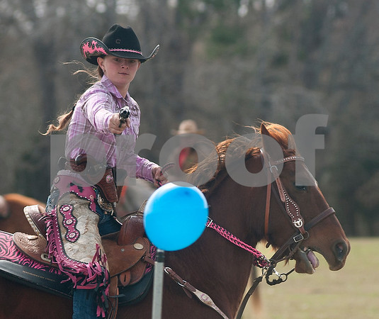 photo by Sarah A. Miller/Tyler Morning Telegraph  Shelby Degeare, 16, of Sanger, Texas, shoots a blank cartridge at a balloon target with a .45 pistol during the Cowboy Mounted Shooting event at the 1836 Chuckwagon Race in Neches, Texas Friday March 7, 2014. The 1836 Chuckwagon Race at Diamond B Ranch is a week long celebration of western culture centering around Texas Independence Day weekend. Cowboy Mounted Shooting is a timed event where competitors use two pistols while riding a horse or mule through balloon targets. Each balloon missed is a five second penalty.