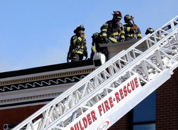 Fire fighters gather on the roof while combating the structure fire at 14th and Pearl Street in Boulder, Colorado March 9, 2011.  CAMERA/Phil McMichael