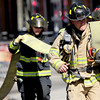 Fire fighters race down the street carrying a large hose to connect to the fire hydrant while working to contain a structure fire at 14th and Pearl Street in Boulder, Colorado March 9, 2011.  CAMERA/Mark Leffingwell