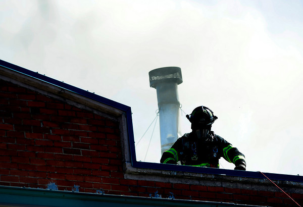 Smoke billows from the roof behind a fire fighter at 14th and Pearl Street in Boulder, Colorado March 9, 2011.  CAMERA/Mark Leffingwell