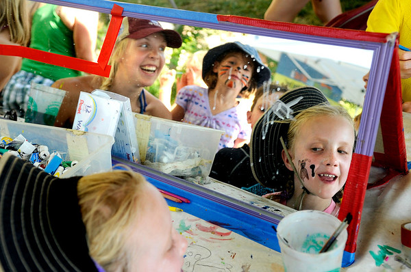 "Ella House, 7, of Charlottesville, Virginia, right, looks in the mirror at her painted face on Saturday, July 30, during the 39th annual RockyGrass Festival at The Planet Bluegrass Ranch in Lyons. For more photos and a video of the festival go to  <a href=""http://www.dailycamera.com"">http://www.dailycamera.com</a><br /> Jeremy Papasso/ Camera"