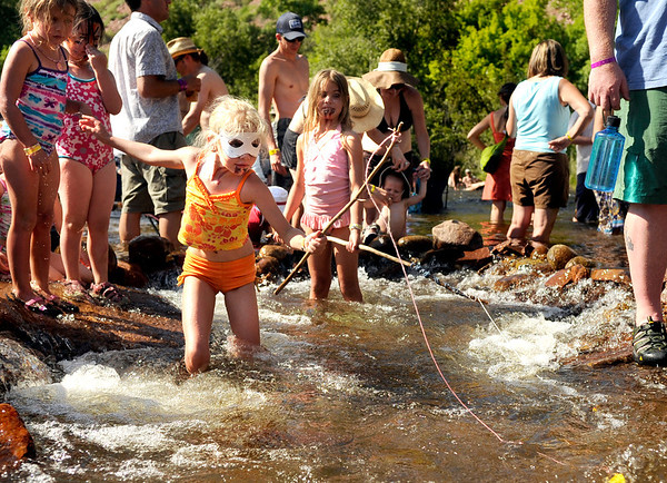"""Sedona Clifford, 7, of Longmont, in orange swimsuit, tries to catch a fish on Saturday, July 30, during the 39th annual RockyGrass Festival at The Planet Bluegrass Ranch in Lyons. For more photos and a video of the festival go to  <a href=""""http://www.dailycamera.com"""">http://www.dailycamera.com</a><br /> Jeremy Papasso/ Camera"""