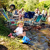 """Amanda Parik Johansson, of Sweden, sits by the waters edge playing with her bucket and tools on Saturday, July 30, during the 39th annual RockyGrass Festival at The Planet Bluegrass Ranch in Lyons. For more photos and a video of the festival go to  <a href=""""http://www.dailycamera.com"""">http://www.dailycamera.com</a><br /> Jeremy Papasso/ Camera"""