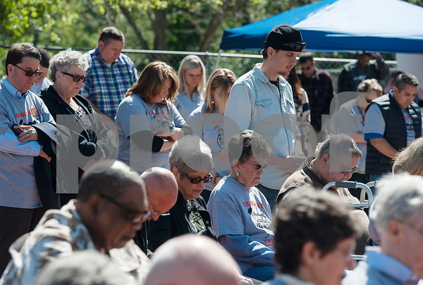Supporters of Hiway 80 Rescue Mission bow for a prayer as they attend a demolition day for old structures on the site for the organization's new Triumph Village site in Tyler on Tuesday April 19, 2018.   (Sarah A. Miller/Tyler Morning Telegraph)