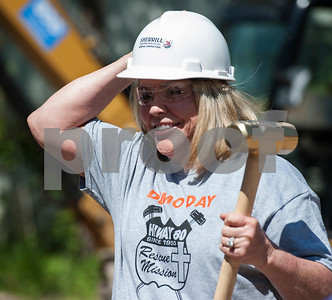 Jessie Enright puts on a hard hat as she picks up a golden sledgehammer to start the demolition progress of an old structure on the site of Hiway 80 Rescue Mission's Triumph Village in Tyler on Tuesday April 19, 2018.   (Sarah A. Miller/Tyler Morning Telegraph)