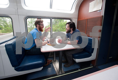 "photo by Sarah A. Miller/Tyler Morning Telegraph  Dwight Veleker and Henry Parker drink beers in the lounge car as they ride the Texas Eagle route on the Amtrak train Thursday April 9, 2015. The two friends were traveling from Madison, Wisconsin to Austin, Texas. The Amtrak train offers coach cars, a lounge car, a sleeper car and dining car along this route. ""Everyone who is here has been very interesting to talk to. People take the train to meet interesting people,"" Parker said."