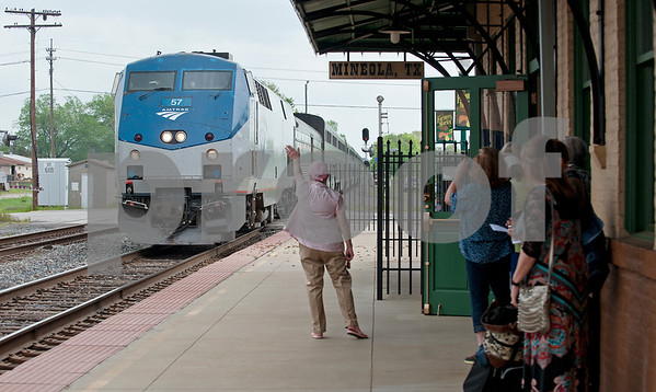 photo by Sarah A. Miller/Tyler Morning Telegraph  Mineola station host Martha Moreland waves to the conductor as the Texas Eagle Amtrak train arrives Thursday April 9, 2015. The Amtrak train offers coach cars, a lounge car, a sleeper car and dining car along this route stopping in 41 cities from Chicago to Los Angeles.