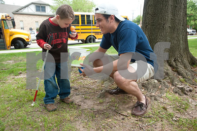 photo by Sarah A. Miller/Tyler Morning Telegraph  Evan Thomas, 7, of Flint, receives an Easter egg from volunteer Nadim Aly of Tyler during the third annual Lighthouse Easter Egg Hunt at Bergfeld Park Thursday afternoon. The event featured beeping eggs for blind children and jumbo sized eggs for visually impaired children. East Texas Lighthouse for the Blind, Texas Department of Assistive and Rehabilitative Services and Tyler Independent School District volunteers helped run the event. The Easter egg hunt was an opportunity for visually impaired children to improve their orientation and mobility, their recreation and leisure skills and social skills.