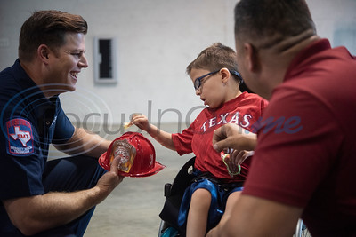 Firefighter James Branch gives a fire hat to Evan Valle, 5, of Lindale, after a press conference at Tyler Fire Station No. 7 announcing their kick-off to raise money for the Muscular Dystrophy Association on Wednesday April 17, 2019. The Tyler Fire Department's Fill the Boot campaign is aiming tp raise $70,000 for MDA.   (Sarah A. Miller/Tyler Morning Telegraph)