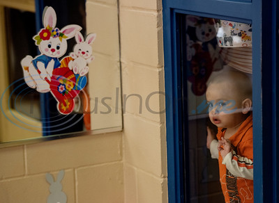A young boy puts his face to the window to watch as older children collect as many eggs as they can in one minute at the Tyler Parks and Recreation's 18th Annual Twilight Easter Egg Hunt at the Glass Recreation Center on Thursday April 18, 2019.   (Sarah A. Miller/Tyler Morning Telegraph)