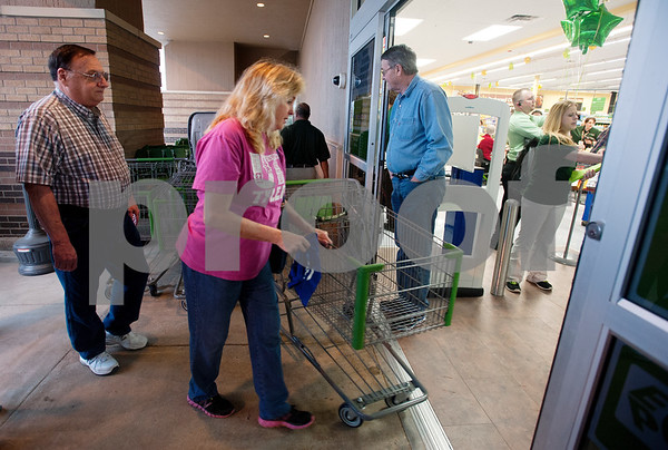 photo by Sarah A. Miller/Tyler Morning Telegraph  Some of the first customers line up to get shopping carts at the new Walmart Neighborhood Market during their first hour of business Wednesday morning. The store, located at 1900 ESE Loop 323 in Tyler, offers quick and convenient shopping, with a full-grocery department featuring prepared food options, fresh baked breads, gluten-free options, a deli and a bakery. It also has a pharmacy.