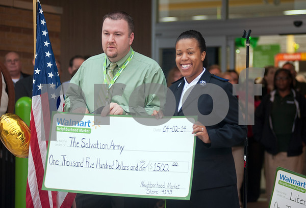 photo by Sarah A. Miller/Tyler Morning Telegraph  David Price, store manager of the new Walmart Neighborhood Market handed out several checks to community charities including The Salvation Army, pictured here, before the store opened Wednesday morning. The store, located at 1900 ESE Loop 323 in Tyler, offers quick and convenient shopping, with a full-grocery department featuring prepared food options, fresh baked breads, gluten-free options, a deli and a bakery. It also has a pharmacy.