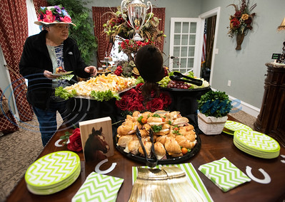 Prestige Estates resident Nancy Duress, 82, wears a flower decorated hat as she gets a food plate before the start of the Kentucky Derby stick-horse race at the assisted living facility in Tyler on Tuesday April 23, 2019.   (Sarah A. Miller/Tyler Morning Telegraph)