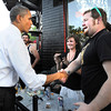 President Barack Obama shakes hands with Dan Williams, of Boulder, outside of The Sink restaurant on University Hill in Boulder in an unexpected detour from the Coors Events Center before his speech on Tuesday April 24, 2012. Obama took a box of pizza to his motorcade. <br /> Photo by Jeremy Papasso April 24, 2012
