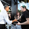 OBAMA1a.jpg President Barack Obama shakes hands with Dan Williams, of Boulder, outside of The Sink restaurant on University Hill in Boulder in an unexpected detour from the Coors Events Center before his speech on Tuesday April 24, 2012. Obama took a box of pizza to his motorcade. <br /> Photo by Jeremy Papasso April 24, 2012