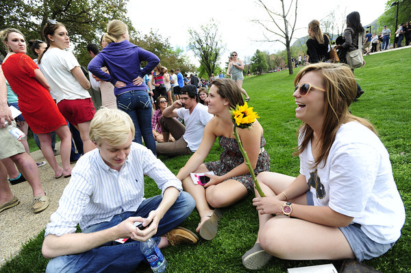 From left to right, CU students, David Gillis, Andrea Meli and Alexis Scobio take a seat as they wait in the long line  to get into the President Obama speech on the CU Campus on Tuesday. The line snaked all over campus. <br /> Photo by Paul Aiken April 24, 2012
