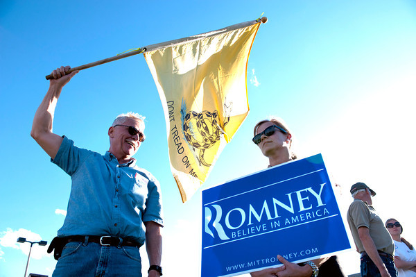 From left Steve Sample and Betsy McCain hold Romney signs as protestors line the hill awaiting the Presidential Motorcade on Colorado Blvd before the Obama speech<br /> Photo by Jonathan Castner April 24, 2012