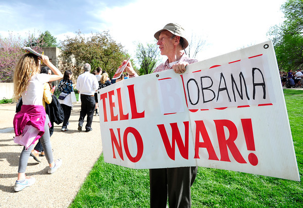 Dan Winters holds a protest sign as  looks the line to the President Obama speech snakes around on the CU Campus on Tuesday.<br /> Photo by Paul Aiken April 24, 2012