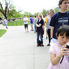 Silu Gu, 8, takes photos of the long line waiting to get into the President Obama speech on the CU Campus on Tuesday. The line snaked all over campus. <br /> Photo by Paul Aiken April 24, 2012