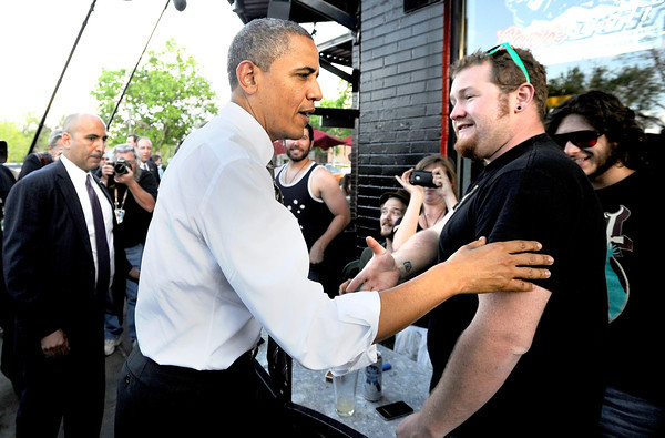 President Barack Obama greets customers of The Sink restaurant on University Hill in Boulder in an unexpected detour from the Coors Events Center before his speech on Tuesday April 24, 2012. Obama took a box of pizza to his motorcade. <br /> Photo by Jeremy Papasso April 24, 2012
