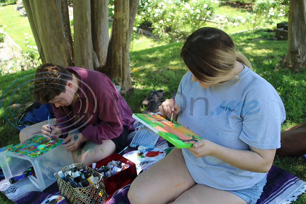 Ethan Masters and Mackenzie Guess paint during the 13th Annual Art in the Garden event at the Tyler Rose Garden.