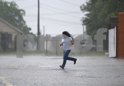 A girl runs in the rain through the La Michoacana Meat Market Friday April 29, 2016 in Tyler. Possible tornado activity near occurred in the East Texas area Friday April 29, 2016.   (Sarah A. Miller/Tyler Morning Telegraph)