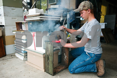 photo by Sarah A. Miller/Tyler Morning Telegraph  Gabe Sullens, 13, of Overton, starts the smoker for beekeeper Dick Counts to use to calm the bees before opening up a hive box in his yard Thursday. Counts offers a beekeeping class, and Sullens is one of his students.
