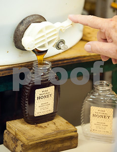 photo by Sarah A. Miller/Tyler Morning Telegraph  Beekeeper Dick Counts fills a container with honey from his hives at his home in Chapel Hill. Counts is president of the East Texas Beekeepers Association.