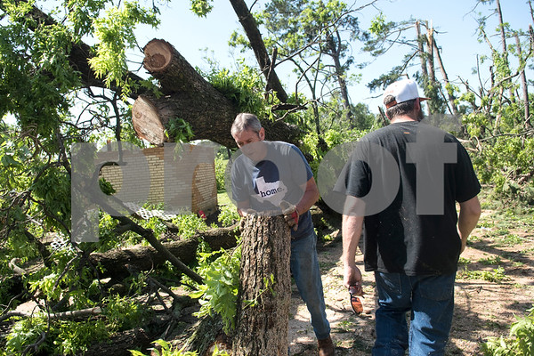 Danny Barnett and Aryn Parson work around fallen trees in their relative's backyard on Farm-to-Market 16 in Lindale, Texas Saturday morning April 30, 2016. A suspected tornado came through the area Friday night. The home owned by Mary and Andy Anderson was damaged by falling trees.  (Sarah A. Miller/Tyler Morning Telegraph)