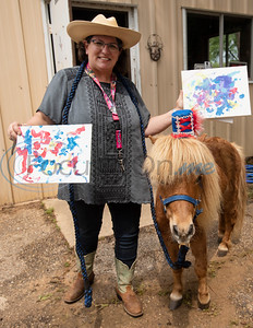 Adrain Hurst holds some of Chismo the Painting Pony's artwork at Camp V, which is one of the organizations receiving funds through East Texas Giving Day on Tuesday April 30, 2019. Camp V is raising money to renovate buildings on the property to bring multiple veterans' services together onto one campus. Chismo is part of THAAT Ranch, one of the vendors that will serve veterans at Camp V through equine therapy.   (Sarah A. Miller/Tyler Morning Telegraph)