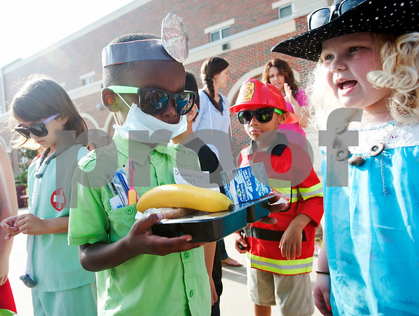 photo by Sarah A. Miller/Tyler Morning Telegraph  Kindergartener La'Darrion Dews, 5, carries a Meals on Wheels meal while dressed as a dentist during a career and community day Thursday April 9, 2015 at Jack Elementary School in Tyler. The day was meant to introduce students to different careers and to help them understand the roles of community leaders such as government officials, non-profit organization leaders and public safety personnel.